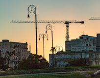 Construction cranes can be seen over Havana skyline at dusk. Havana, Cuba Nov 19, 2017 - Construction cranes can be seen over Havana skyline at dusk stock images