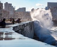 Fishermen stand their ground as waves crash over the Malecon wal Royalty Free Stock Images