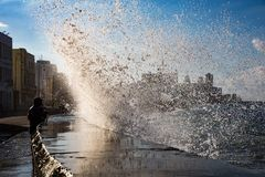 Fishermen stand their ground as waves crash over the Malecon wal Stock Images