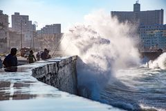 Fishermen stand their ground as waves crash over the Malecon wal Royalty Free Stock Photo
