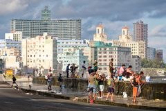 Fishermen at the famous Malecon seawall in Havana. HAVANA,CUBA - NOVEMBER 25,2017 : Fishermen at the famous Malecon seawall in Havana with a view of the city Stock Photos