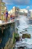 Fishermen at the famous Malecon seawall in Havana. HAVANA,CUBA - NOVEMBER 25,2017 : Fishermen at the famous Malecon seawall in Havana with waves crashing on the Stock Images