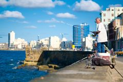 People fishing on the Malecon seawall in Havana. HAVANA,CUBA - NOVEMBER 6, 2017 : People fishing on the Malecon seawall in Havana with a view of the city skyline Stock Photos