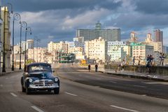 Urban scene with old car at the famous Malecon seawall in Havana. HAVANA,CUBA - NOVEMBER 25,2017 : Urban scene with old car at the famous Malecon seawall in Royalty Free Stock Photo