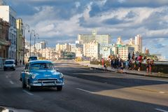 Urban scene with old car at the famous Malecon seawall in Havana. HAVANA,CUBA - NOVEMBER 25,2017 : Urban scene with old car at the famous Malecon seawall in Stock Images