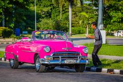 HAVANA, CUBA-OCT 25- Tourist enjoys a photo op in an antique cars used as taxis in Havana, on October 25, 2015 stock photo