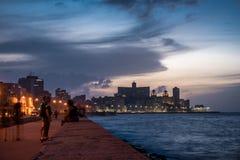 HAVANA, CUBA - OCTOBER 22, 2017: Havana Cityscape with Malecon Avenue and Caribbean Sea in Background. Blurry People Because of Lo. Havana Cityscape with Malecon Stock Photo