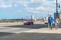 HAVANA, CUBA - OCTOBER 23, 2017: Havana Cityscape with Malecon Avenue. Tourist and Old Vehicle in Background. Havana Cityscape with Malecon Avenue. Tourist and Stock Photography