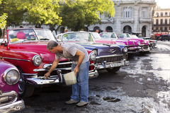 HAVANA, CUBA-OCTOBER 14: Man washing old car on streets of Havan Royalty Free Stock Photos