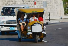 Tourists enjoy trip by the motorbike taxi, known as Coco taxi, at Malecon avenue in Havana, Cuba. HAVANA, CUBA - OCTOBER 21, 2006: Unidentified tourists enjoy Royalty Free Stock Photo