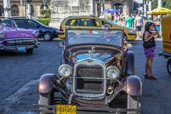 Havana / Cuba - 07/2018: Old and rusty cars of fifties on Havana streets. Brown ones rented on the front view, the pink one on the stock photography