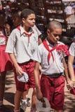 Havana, Cuba - Sept. 2018: De groep leerlingen in eenvormig, twee jongens die samen op de voorzijde gaan stock foto
