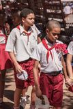 Havana, Cuba - Sept. 2018: The group of pupils in uniform, two boys going together on the front. stock photo