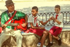 Havana / Cuba - Sept 2018: Old musician plays guitar sitting near to two cuban pupils - boys in red and white uniform stock photography