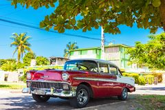 American red white 1956 Chevrolet Bel Air classic car parked under palms in the side street in. Havana City Cuba - Serie Cuba Reportage royalty free stock photo