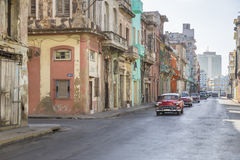 HAVANA CUBAN BUILDINGS AND LIGHT OLD TRAFFIC. Old buildings and old cars riding over old havana street Royalty Free Stock Photo