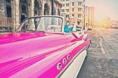 HAVANA 27 DE JANEIRO DE 2013: A mulher bonita anos de um carro retro americano velho da roda em 50th do século passado, uma vista Imagens de Stock Royalty Free
