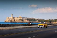 HAVANA - FEBRUARY 17: Classic car and lighthouse in the backgrouClassic old car on streets of Havana, Cuba. Stock Images