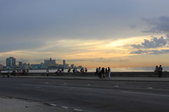 Havana Malecon and people at sunset. People walking in Havana Malecon at sunset Stock Photos