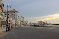 Havana Malecon at sunset. People crossing the street in front of Havana Malecon Stock Images