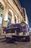 Havana at night. A purple classic car in front of a colonial building at night in Havana, Cuba royalty free stock image