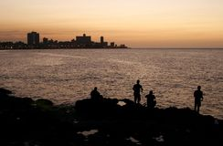Havana seaside (Malecon) at sunset, Cuba. Havana seaside (Malecon) at sunset, silhouettes of fishermen on the foreground Royalty Free Stock Photo