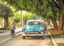Havana street scene with oldtimer. Havana street scene with a blue car and a passing motorcycle Royalty Free Stock Photo