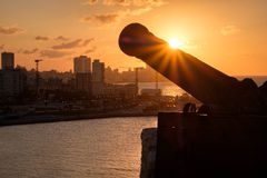 Havana at sunset with the silhouette of an old cannon on the foreground Stock Photos