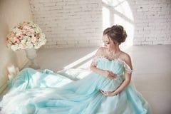 Havandeskap, kvinnasammanträde på golvet i en lyx- klänning och håll Royaltyfri Foto