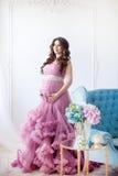 Havandeskap-, moderskap- och förväntanbegrepp - en iklädd gravid kvinna en härlig rosa färg klär Fotografering för Bildbyråer