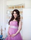 Havandeskap-, moderskap- och förväntanbegrepp - en iklädd härlig rosa aftonklänning för gravid kvinna Fotografering för Bildbyråer