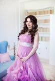 Havandeskap-, moderskap- och förväntanbegrepp - en iklädd rosa aftonklänning för gravid kvinna ler Royaltyfri Bild
