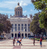 HAVANNACIGARR KUBA - APRIL 1, 2012: Unga pojkar som spelar fotboll nära revolutionmuseum Royaltyfria Foton
