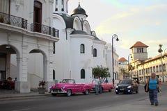 Havannacigarr Kuba - September 1st 2017: Ortodox kyrkliga och kubanska bilar på gatan Fotografering för Bildbyråer