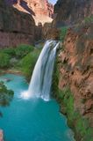 Havasu Falls at Dusk. Havasu Falls drops into an aquamarine pool below while the last light of the day hits the high cliffs in the background Royalty Free Stock Photo