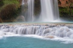 Havasu Falls and Travertine Cascades. Aquamarine water flows over travertine cascades with Havasu Falls in the background Stock Photos
