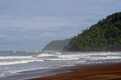 Havbränningen som slår stranden och, seglar utmed kusten Arkivbild