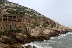Have abandoned the most eastern end of the fishing village in China. Village threatened by rock tumbled and waves was abandoned stock photo
