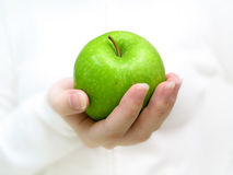 Have an apple 2. Close up front profile of a woman holding a green apple toward the camera royalty free stock images