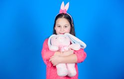 Have blessed Easter. Bunny girl with cute toy on blue background. Child smiling play bunny toy. Happy childhood. Get in. Easter spirit. Bunny ears accessory stock photography