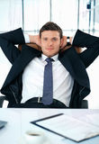 Have a Brake. Young businessman sitting with his hands under his head looking at you Stock Photo