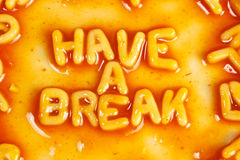 Have a break. Alphabet shaped pasta forming HAVE A BREAK in tomato sauce Stock Photography