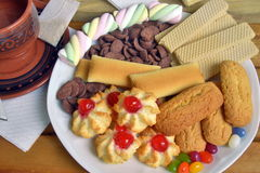 Have breakfast at home with tea and biscuits. Closeup of a plate filled with cookies of various kinds. Near a teapot and a cup Stock Photos
