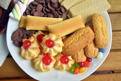 Have breakfast at home with tea and biscuits. Closeup of a plate filled with cookies of various kinds. Near a teapot and a cup Stock Images
