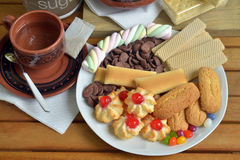 Have breakfast at home with tea and biscuits. Closeup of a plate filled with cookies of various kinds. Near a teapot and a cup Royalty Free Stock Photography