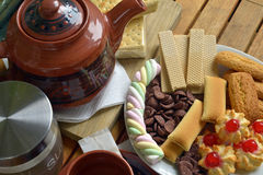 Have breakfast at home with tea and biscuits. Closeup of a plate filled with cookies of various kinds. Near a teapot and a cup Stock Image