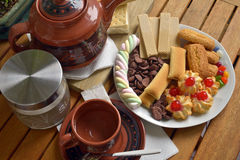 Have breakfast at home with tea and biscuits. Closeup of a plate filled with cookies of various kinds. Near a teapot and a cup Royalty Free Stock Photo