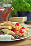Have breakfast at home with tea and biscuits. Closeup of a plate filled with cookies of various kinds. Near a teapot and a cup Stock Photo