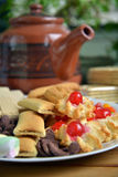 Have breakfast at home with tea and biscuits. Closeup of a plate filled with cookies of various kinds. Near a teapot and a cup Stock Photography