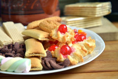 Have breakfast at home with tea and biscuits. Closeup of a plate filled with cookies of various kinds. Near a teapot and a cup Royalty Free Stock Image
